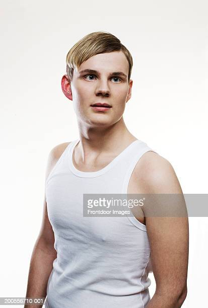 Young man in white vest, looking away, close-up