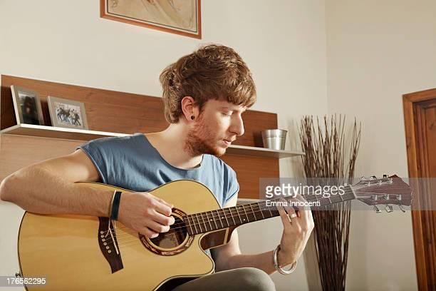 Young man indoor playing guitar