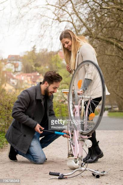 young man inflating bicycle tire for his girlfriend - doing a favor stock pictures, royalty-free photos & images