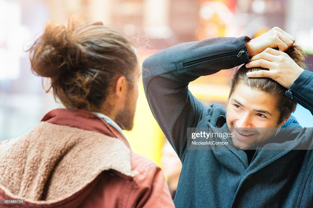 Young man influenced by friend to make a man bun : Stock Photo