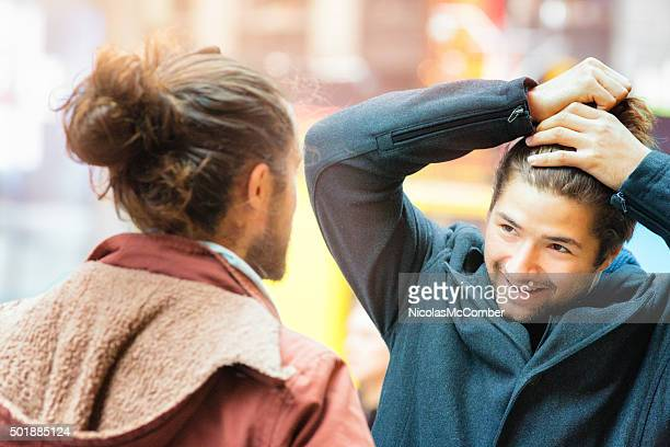 young man influenced by friend to make a man bun - man bun stock pictures, royalty-free photos & images