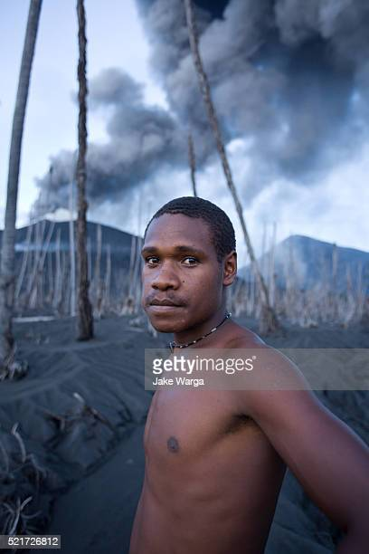 young man infront of mt. tavurvur, rabaul, papua new guinea - jake warga stock pictures, royalty-free photos & images