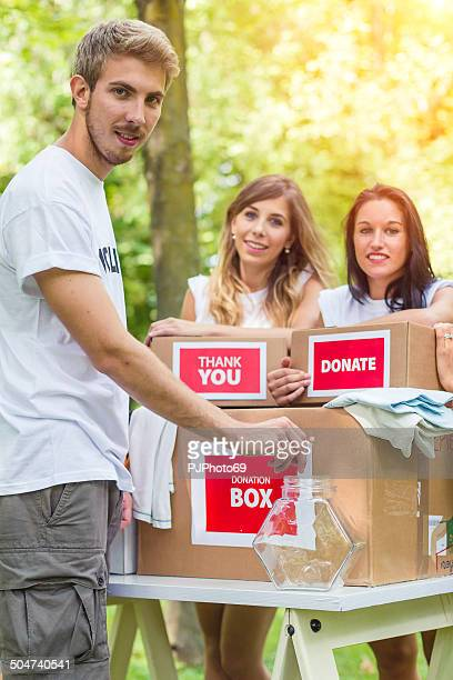 young man insert coin on donation box - pjphoto69 stockfoto's en -beelden