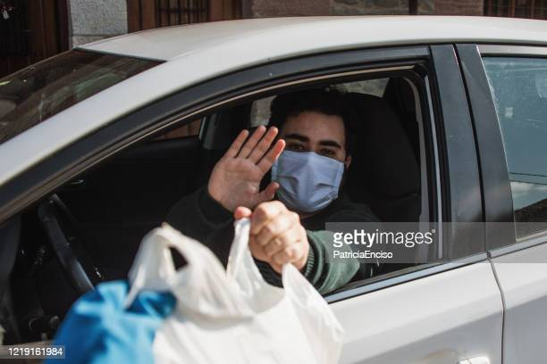 young man inside a car wearing a face mask receiving a bag with food - driving mask stock pictures, royalty-free photos & images