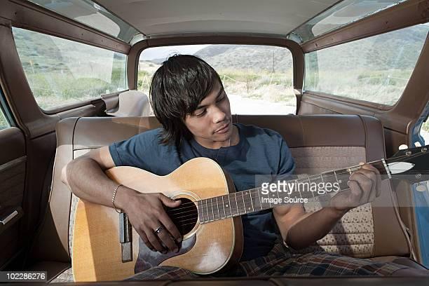 Jeune homme jouant de la guitare à l'intérieur de voiture