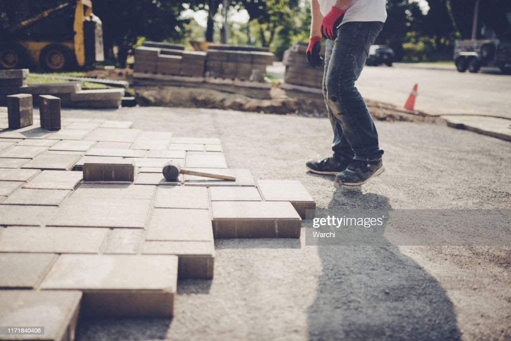Young man installing paving stones for a new driveway : Foto de stock