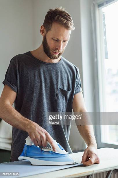 Young man ironing in house