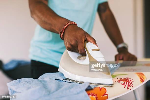 Young man ironing shirt at home
