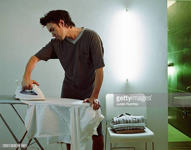 Young man ironing shirt