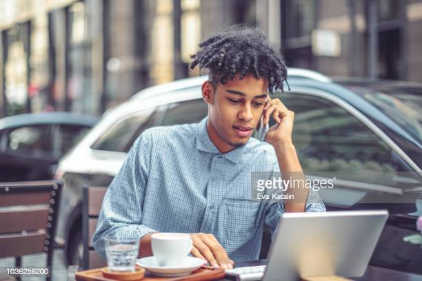 young man is blogging from a sidewalk caffee - millennial generation stock pictures, royalty-free photos & images