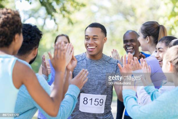young man is congratulated  with high fives after race - charity benefit stock pictures, royalty-free photos & images