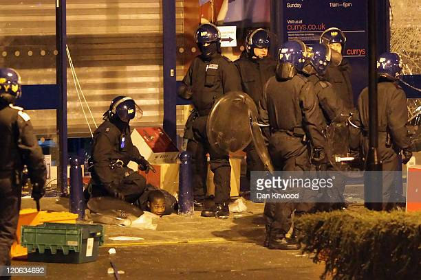 A young man is detained outside the Currys electrical store in Brixton on August 8 2011 in London England Widespread rioting and looting took place...