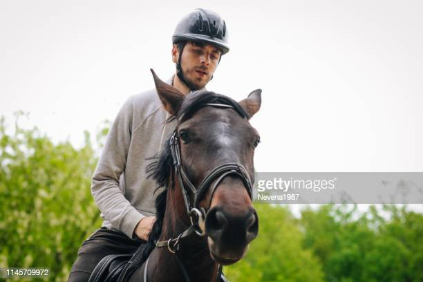 junger mann genießt reiten in der natur - zwischen die beine greifen stock-fotos und bilder