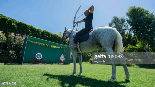 Young man is enjoying horseback shooting archery  in nature