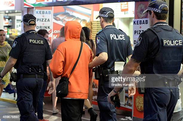 A young man is escorted away by Police during Australian 'schoolies' celebrations following the end of the year 12 exams on November 28 2014 in Gold...