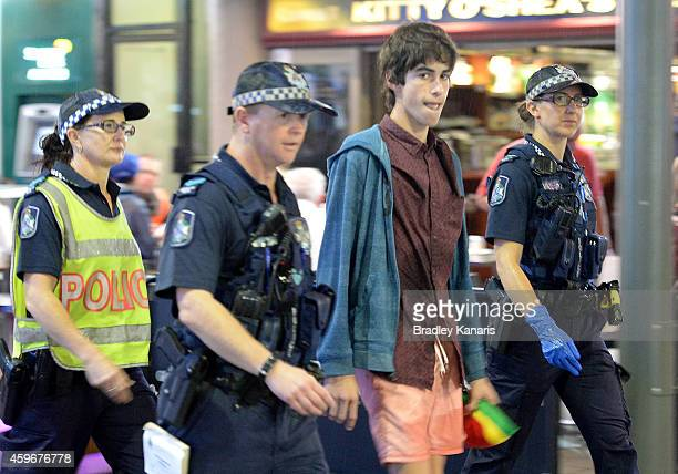 A young man is escorted by Police during Australian 'schoolies' celebrations following the end of the year 12 exams on November 28 2014 in Gold Coast...