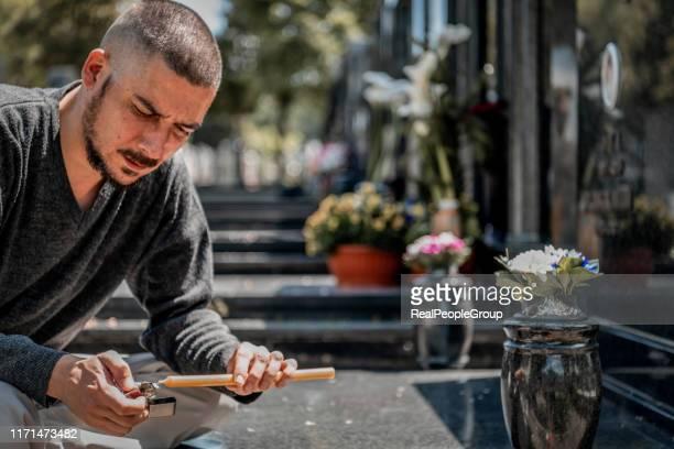 el hombre joven se siente triste debido a perder a la persona más cercana.hombre emocionalmente estresado con una vela en el cementerio - luto fotografías e imágenes de stock