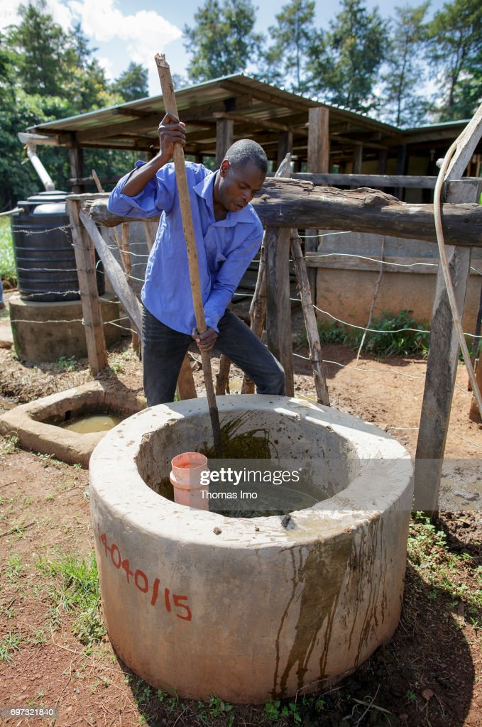 A young man is filling a biogas plant at the Bukura