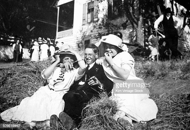 A young man is happily wedged between two women in a pile of hay at a backyard party