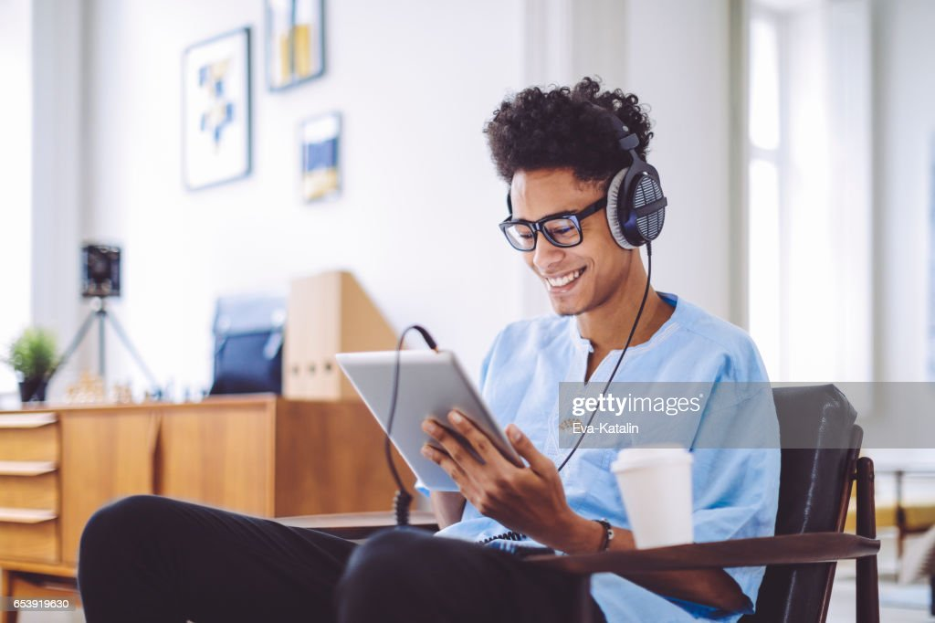 Young man is listening music at home : Stock Photo