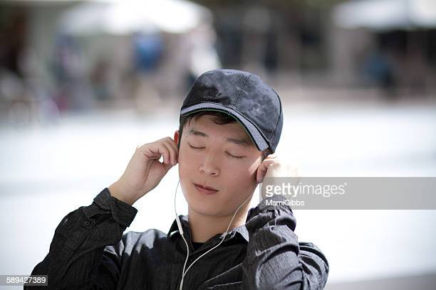 young man is listening to music - mamigibbs stock photos and pictures