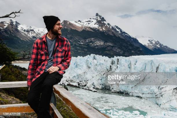a young man is looking at perito moreno glacier at los glaciares national park in patagonia, argentina - glacier collapsing stock pictures, royalty-free photos & images