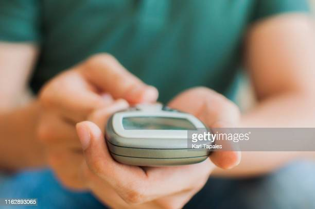 a young man is measuring his blood sugar - glucose stock pictures, royalty-free photos & images
