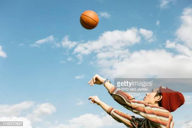 young man is playing basketball. - バスケットボールのシュート ストックフォトと画像