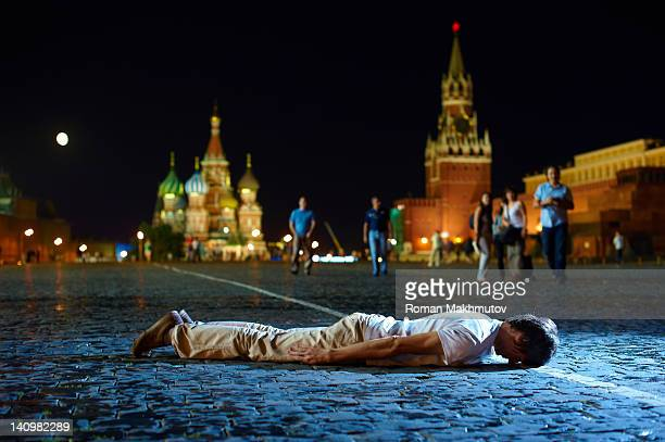 Young man is playing Planking, or Lying Down Game, on the Red Square. Moscow, Russia.