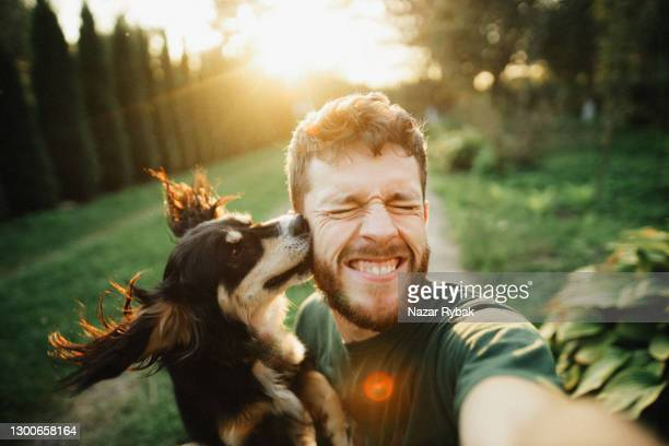 young man is playing with a dog and do selfie - ukraine stock pictures, royalty-free photos & images