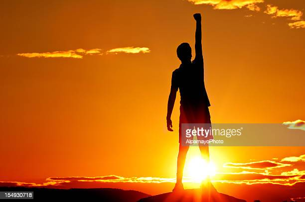 young man is punching air in celebration, sunset scenery (ii) - punching the air stock pictures, royalty-free photos & images