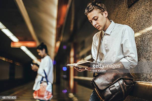 Young man is reading a book on the underground
