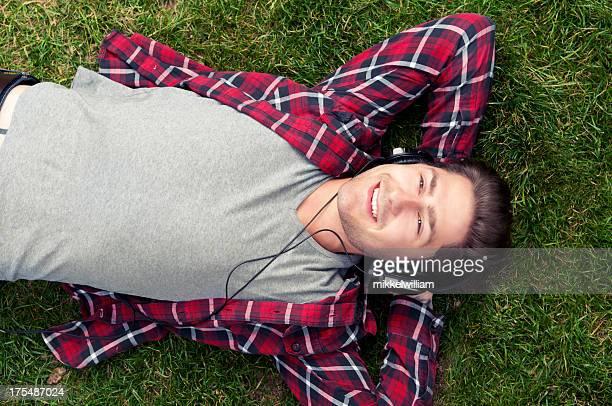 Jovem é relaxante na grama ouvir música