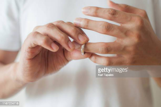 a young man is removing his wedding ring a concept of relationship difficulties - cornuto foto e immagini stock