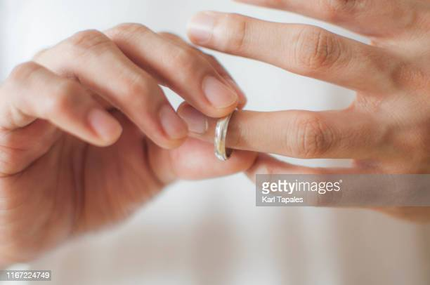 a young man is removing his wedding ring a concept of relationship difficulties - white gold stock pictures, royalty-free photos & images