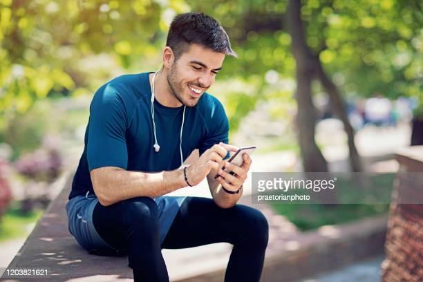 junger mann ruht sich aus und textet nach dem lauf im park - sportsperson stock-fotos und bilder