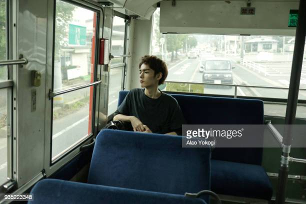 young man is riding alone by bus - chiba bus ストックフォトと画像