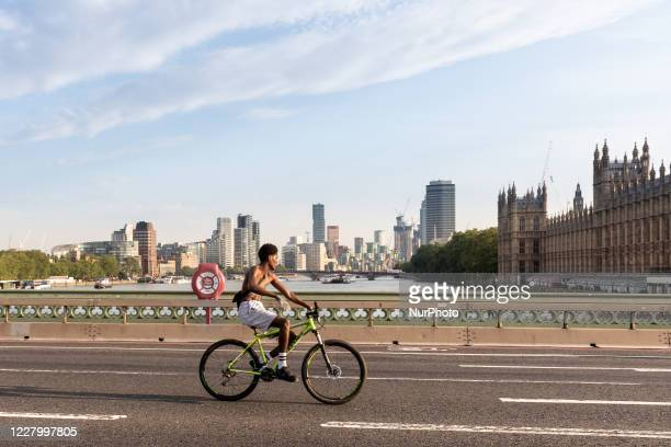 Young man is seen riding his bike on Westminster Bridge on a particularly hot day of summer tourism season as London encourages internal tourism...