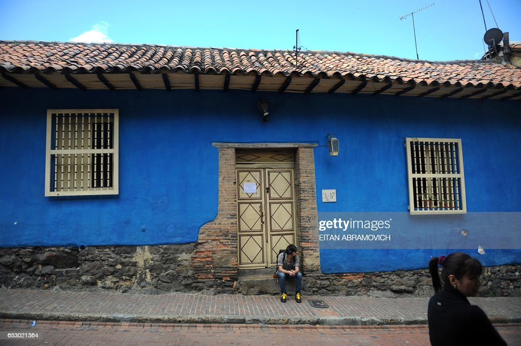 A young man is seen sitting in a doorstep of a typical house in the historic neighborhood of La Candelaria in Bogota on September 17, 2009. La Candelaria is Bogota's oldest neighbourhood and the city's historical center, known for its colonial houses with wooden balconies and clay shingle roofs. AFP PHOTO/Eitan Abramovich /