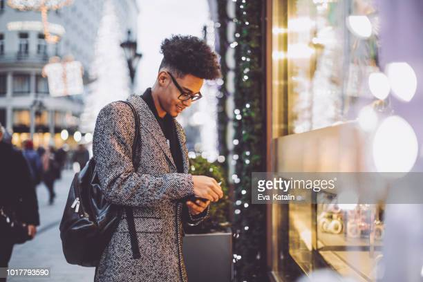 young man is shopping for christmas presents - african american christmas images stock pictures, royalty-free photos & images