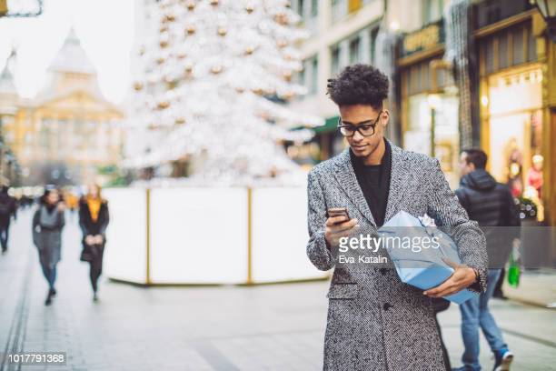 young man is texting and holding a christmas present - christmas shopping stock photos and pictures