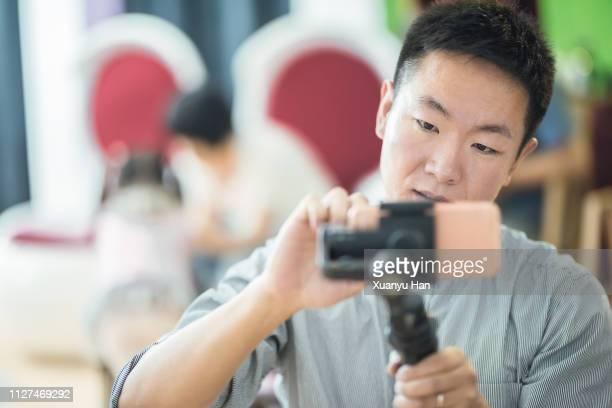 young man is using mobile phone - tripod stock pictures, royalty-free photos & images
