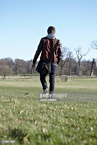 A young man is walking in a park