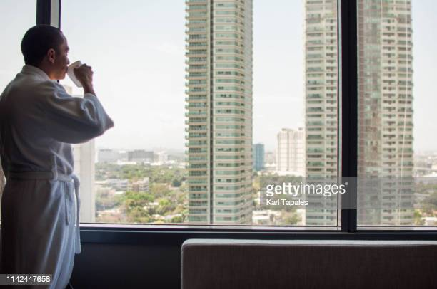 a young man is wearing a bathrobe while drinking a cup of coffee - daily life in philippines stock pictures, royalty-free photos & images