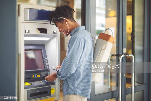 young man is withdrawing money from an atm - atm stock pictures, royalty-free photos & images