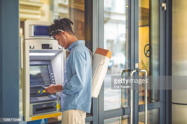 young man is withdrawing money from an atm - bank financial building stock pictures, royalty-free photos & images