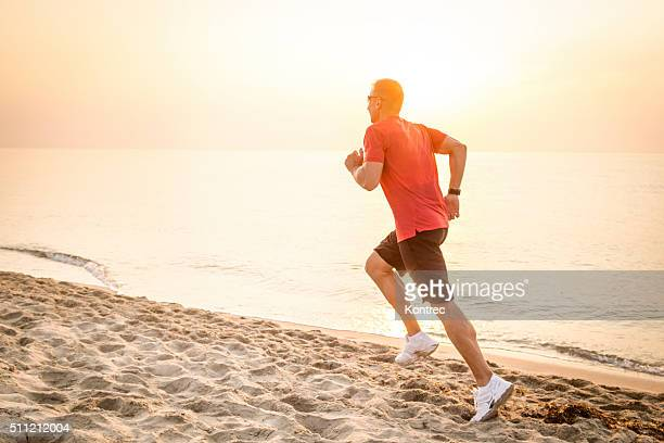 Young man jogging at the sandy beach