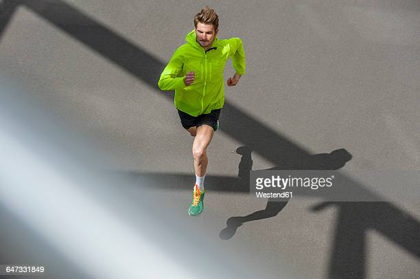 Young man jogging, concrete floor