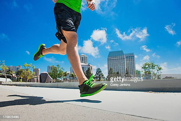Young man jogging in city, low section