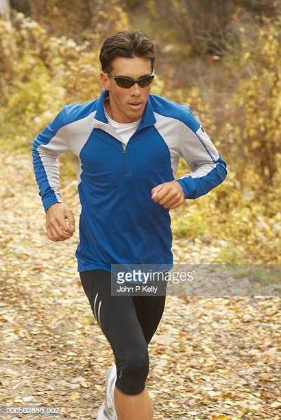 young man jogging on dirt track in autumn - コロラド州 ニューキャッスル ストックフォトと画像